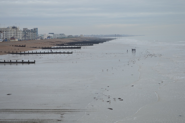 Early morning walkers on the beach, seen from the pier, looking east