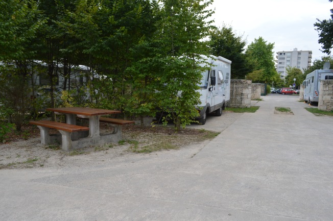 Our pitch at Motorhome aire at Niort, with hedges and stone walls separating parking bays